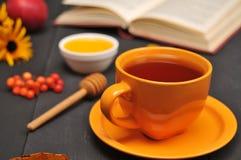 Do outono copo da vida ainda do chá, do mel e do livro na tabela Imagens de Stock