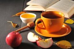 Do outono copo da vida ainda do chá, do mel e do livro na tabela Imagem de Stock