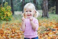 Do outono da floresta da menina nos gritos louros pequenos entusiasticamente Fotos de Stock Royalty Free