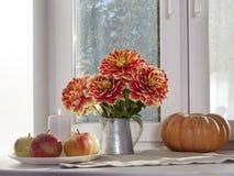 Do outono a vida ainda com as dálias vermelhas em um frasco da lata, na abóbora, em um copo do chá e em maçãs na janela no tempo  Fotografia de Stock Royalty Free