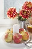 Do outono a vida ainda com as dálias vermelhas em um frasco da lata, na abóbora, em um copo do chá e em maçãs na janela no tempo  Imagens de Stock Royalty Free