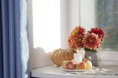 Do outono a vida ainda com as dálias vermelhas em um frasco da lata, na abóbora, em um copo do chá e em maçãs na janela no tempo  Foto de Stock