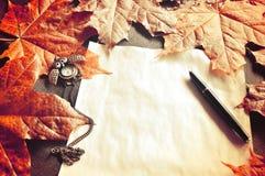 Do outono vida ainda O papel amarelado velho com pulsos de disparo e a tinta encerram perto das folhas de bordo do outono Imagem de Stock Royalty Free
