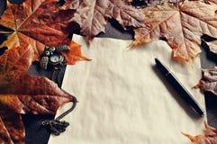 Do outono vida ainda O papel amarelado velho com pulsos de disparo e a tinta encerram perto das folhas de bordo do outono Imagens de Stock Royalty Free