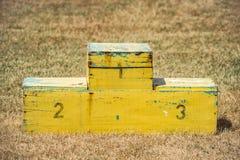 Do pódio do amarelo a cerimônia de madeira feito a mão da competição do suporte fora ostenta a posição vazia Foto de Stock Royalty Free