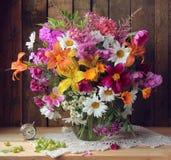 Do país vida ainda com flores em um frasco e em um despertador Imagem de Stock