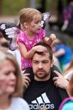 Do pai vestindo dos passeios das asas da criança os ombros no festival da borboleta foto de stock