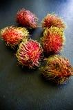 Do Rambutan do fruto vida ainda na mesa de cozinha preta Imagem de Stock