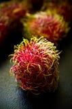Do Rambutan do fruto vida ainda na mesa de cozinha preta Imagens de Stock Royalty Free