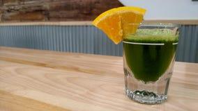 Juice Shots. Raw organic kale juice shot. Orange slice chaser. Immune booster Royalty Free Stock Photo