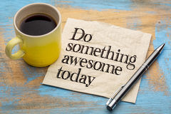 Do something awesome today. Advice or reminder - handwriting on a napkin with a cup of coffee royalty free stock photo