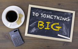 Do Something Big. Chalk board on a wooden table.  Stock Photo