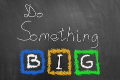 Do something big chalk text on blackboard or chalkboard royalty free stock image