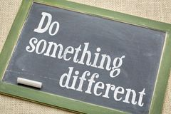 Do something different note on slate blackboard Stock Photography