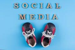Do sumário social dos meios do texto letras de madeira Fundo azul com sapatilhas do bebê Povos que conectam e que compartilham de fotografia de stock