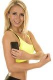 Do sutiã amarelo dos esportes da mulher do direito medida eletrônica do sorriso do bíceps foto de stock royalty free