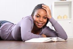 Do tempo a menina do estudante para fora olha acima do livro de leitura Imagem de Stock