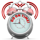 Do on time! The alarm clock with an inscription Stock Images
