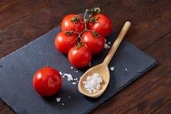 Do vegetariano vida ainda com os tomates, pimento e sal frescos da uva na colher de madeira no fundo de madeira, foco seletivo Fotografia de Stock