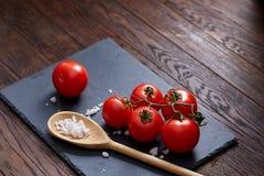 Do vegetariano vida ainda com os tomates, pimento e sal frescos da uva na colher de madeira no fundo de madeira, foco seletivo Imagens de Stock