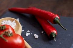 Do vegetariano vida ainda com os tomates, pimento e sal frescos da uva na colher de madeira no fundo de madeira, foco seletivo Imagem de Stock