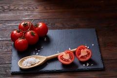 Do vegetariano vida ainda com os tomates, pimento e sal frescos da uva na colher de madeira no fundo de madeira, foco seletivo Fotografia de Stock Royalty Free