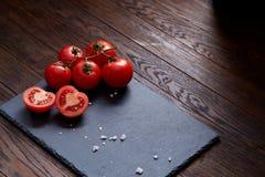 Do vegetariano vida ainda com os tomates, pimento e sal frescos da uva na colher de madeira no fundo de madeira, foco seletivo Foto de Stock Royalty Free