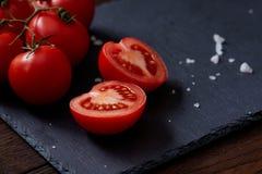 Do vegetariano vida ainda com os tomates, pimento e sal frescos da uva na colher de madeira no fundo de madeira, foco seletivo Foto de Stock