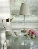 Do verão vida ainda com jarro, lâmpadas de leitura, copo e peônias em uma tabela de vidro Fotografia de Stock