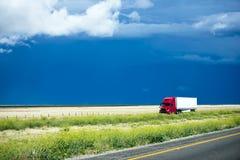 Do vermelho caminhão semi que vai com carga em Califórnia que ajardina a estrada Foto de Stock