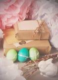 Do vintage da Páscoa vida ainda com ovos pintados, caixas de presente empacotadas dentro no papel de embalagem e o coelho branco  Fotografia de Stock Royalty Free