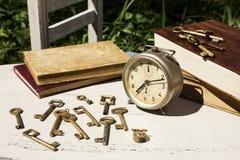 Do vintage vida ainda com despertador velho, chaves e livros Foto de Stock