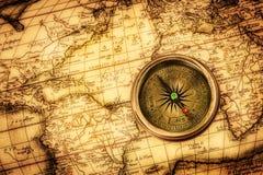 O compasso do vintage encontra-se em um mapa do mundo antigo. Fotos de Stock
