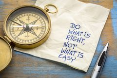 Do what is right, not what easy. Do what is right, not what is easy advice or reminder - handwriting on a napkin with an antique brass compass stock photography