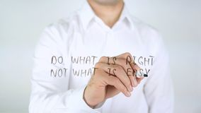Do What Is Right Not What Is Easy, Man Writing on Glass. High quality royalty free stock photography