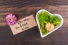 Do what you love to do text on card. With dried flower and heart shape bowl on wood Royalty Free Stock Photo