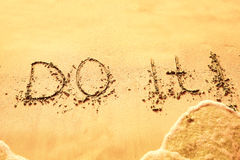 Do it written on sand on beach Royalty Free Stock Photography