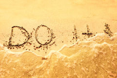 Do it written on sand on beach Stock Photos
