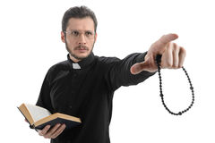 Do you believe in God? Portrait of priest pointing away while st Royalty Free Stock Images