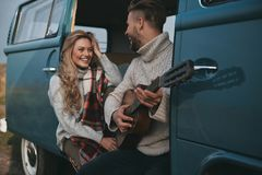 Do you like this song?. Handsome young men playing guitar for his beautiful girlfriend while sitting in blue retro style mini van Stock Photo