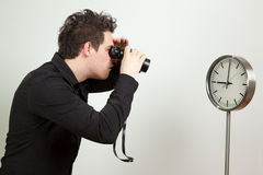 Do you see what time it is?. Guy holding binoculars and looking at the clock royalty free stock photo
