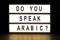 Do you speak Arabic light box sign board. On wooden table Royalty Free Stock Photo