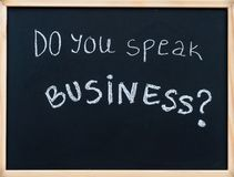 Do you speak business? message written with white chalk on wooden frame blackboard Royalty Free Stock Photo