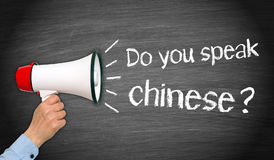 Do you speak chinese - female hand with megaphone and text. On blackboard background royalty free stock photos