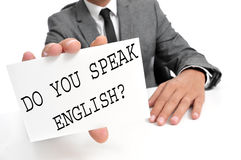 Do you speak english?. A man wearing a suit holding a signboard with the sentence do you speak english? written on it Stock Photos