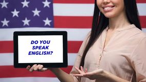 Do you speak English phrase on tablet screen in female hands USA flag background. Stock footage stock footage