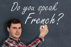 Do you speak French? Man with chalk writing on blackboard. Learning language concept Stock Photo