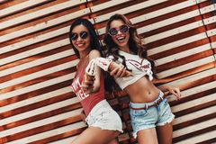 Do you want some?. Two attractive young women smiling and holding ice cream while standing against the wooden wall outdoors royalty free stock photography