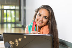 Do your homework with a smile!. Beautiful young woman using laptop while smileing at you Royalty Free Stock Photo