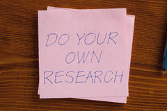 Do your own research written on a note Stock Image